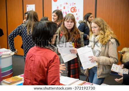 STRASBOURG, FRANCE - FEB 4, 2016: Children and teens of all ages attending annual Education Fair to choose career path and receive vocational counseling - friends receiving advice - stock photo