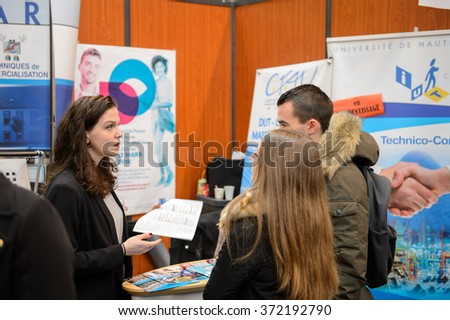 STRASBOURG, FRANCE - FEB 4, 2016: Children and teens of all ages attending annual Education Fair to choose career path and receive vocational counseling - teens receiveing advices at stand - stock photo