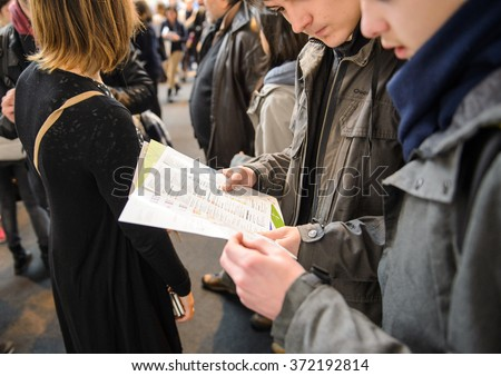 STRASBOURG, FRANCE - FEB 4, 2016: Children and teens of all ages attending annual Education Fair to choose career path and receive vocational counseling - bous reading flyer - stock photo