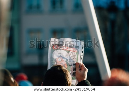 STRASBOURG, FRANCE - 11 JAN, 2015: People holding Charlie Hebdo cover with Mohammed cartoon during a unity rally (Marche Republicaine) where 50000 took part in tribute three-day killing spree in Paris - stock photo