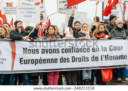 """STRASBOURG, FRANCE - 28 JAN 2015 Turkish protesters hold a banner """"We trust in the European Court of Human Rights during a demonstration near the ECtHR in Strasbourg - stock photo"""
