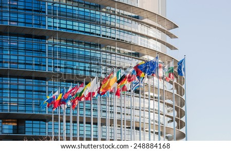 STRASBOURG, FRANCE - JANUARY 28, 2014: European Parliament facade with all EU European Union Country flags waving on a clear sky day. Horizontal shot - stock photo
