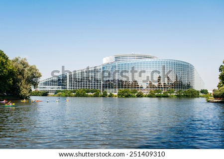 STRASBOURG, FRANCE - JUNE 29: South facade of the European Parliament in Strasbourg, France on June 29 2010 with the intersection of the Ill and Marne-Rhine Canal and canoes. - stock photo