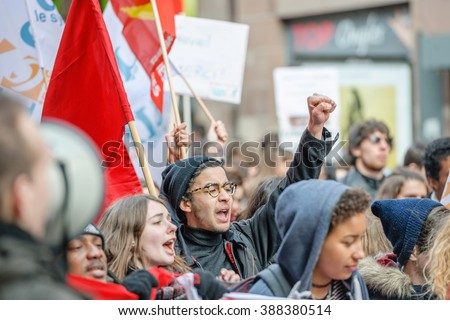 STRASBOURG, FRANCE - 9 MAR 2016 Protester with raised hands in front row of thousands of people demonstrating as part of nationwide day of protest against proposed labor reforms by Socialist Government - stock photo