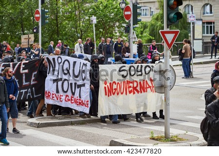 STRASBOURG, FRANCE - MAY 19, 2016: Group of youg people with covered faces holding placards walk with crowd during a demonstrations against proposed French government's labor and employment law reform