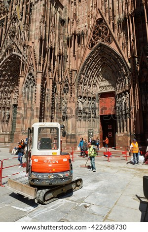 STRASBOURG, FRANCe - MAY 04, 2016: Red Kubota tractor arranging granite pavement sones in from of Strasbourg Cathedral - stock photo