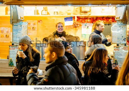 STRASBOURG, FRANCE - NOV 28, 2015: Busy Christmas Market Christkindlmarkt in the city of Strasbourg, Alsace region,  France with smiling woman selling mulled wine