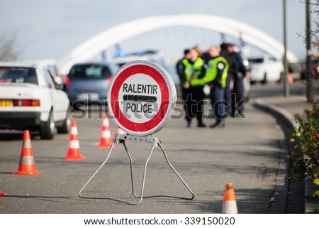 STRASBOURG, FRANCE - NOV 14 2015: French Police checking vehicles on the 'Bridge of Europe' between Strasbourg and Kehl Germany, as a security measure in the wake of attacks in Paris - slow down sign - stock photo