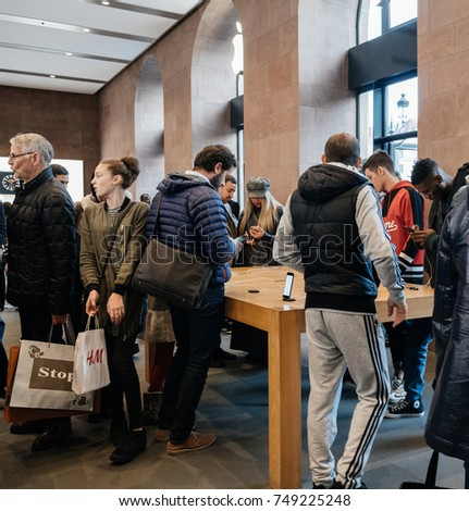 STRASBOURG, FRANCE - NOV 3, 2017: Group of customers at Apple Store Computers admiring deciding to buy the latest iPhone X 10 smartphone telephone