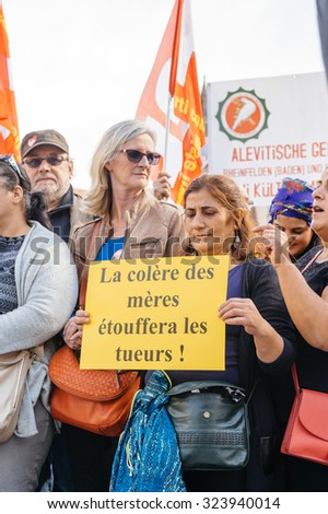 STRASBOURG, FRANCE - OCT 4, 2015 Demonstrators protesting against Turkish President Recep Tayyip Erdogan's visit to Strasbourg - the anger of mothers will suffocate killers placard in women's hands