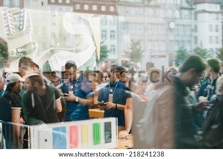 STRASBOURG, FRANCE - SEPTEMBER 19, 2014: Apple Store interior reflected with customers wait in line outside in front the store during the sales launch of the iPhone 6 and iPhone 6 Plus in Europe - stock photo