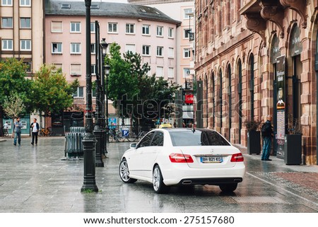 STRASBOURG, FRANCE - SEPTEMBER 21, 2014: White luxury taxi car limousine waiting for customers in front of beautiful french architectural building.  - stock photo