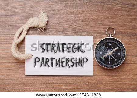 Strategic partnership - business tips handwriting on label with compass - stock photo