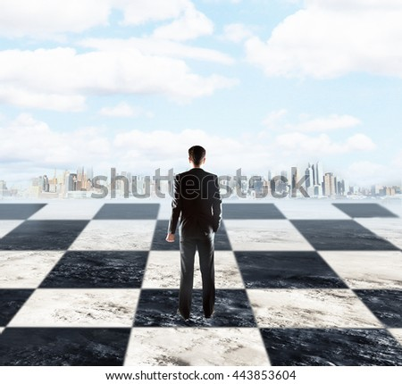 Strategic planning concept with businessman standing on chessboard and looking at city on sky background with clouds