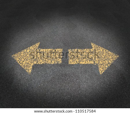 Strategy and decisions concept with a textured asphalt road and two old painted yellow arrows pointing in opposite directions as a business symbol of confusion and uncertainty in the future path. - stock photo