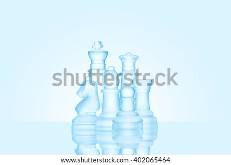 Strategy and leadership concept; frosted chess figures made of ice, standing together as a family ready for game. - stock photo