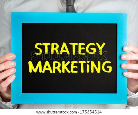 Strategy Marketing handwritten on blackboard which holding man - stock photo