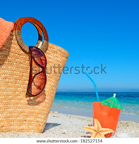 straw bag and drink by the shore
