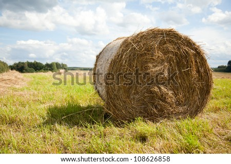 Straw bale / hey stack on golden sunny day with big clouds and blue skies in the background