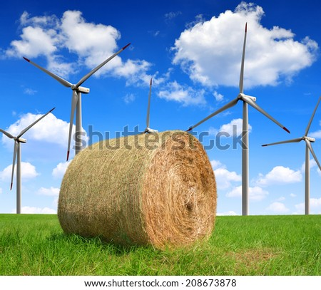 Straw bale on farmland with wind turbines - stock photo