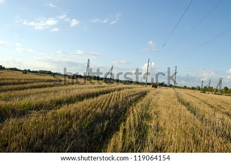 Straw bales in harvested agricultural field electric poles and autumn cloudy sky - stock photo