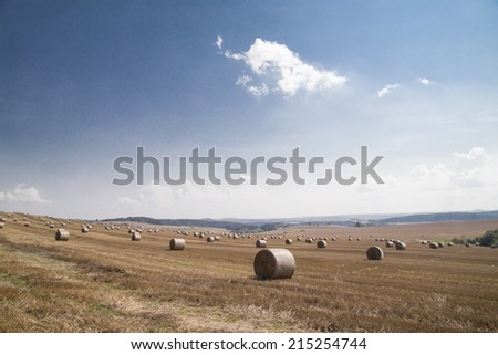 Straw bales on farmland with a blue sky, Czech republic - stock photo
