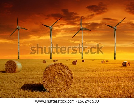 Straw bales with wind turbines in the sunset  - stock photo