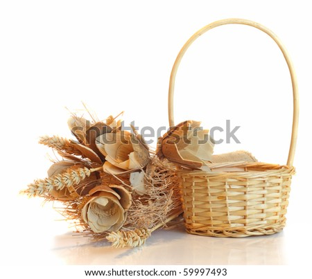 Straw basket and flowers, on white. - stock photo