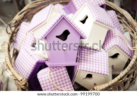 Straw basket full of handmade bird houses - stock photo