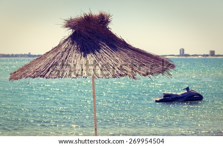 Straw beach umbrella on a background of the cloudless sky and calm sea on a bright sunny day. Toned image. Shallow depth of field. - stock photo