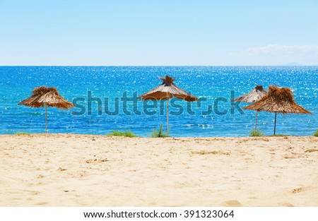 Straw beach umbrellas on a background of  calm sea on a bright sunny day. Selective focus on the parasols. Shallow depth of field.  - stock photo