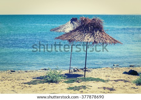 Straw beach umbrellas on a background of  calm sea on a bright sunny day. Toned image. Vintage style photo. Selective focus on the parasol. - stock photo