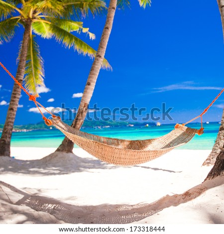 Straw hammock in the shadow of palm on tropical beach by sea - stock photo