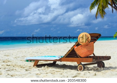 straw hat and bag on a lounge chair at tropical sand beach - stock photo