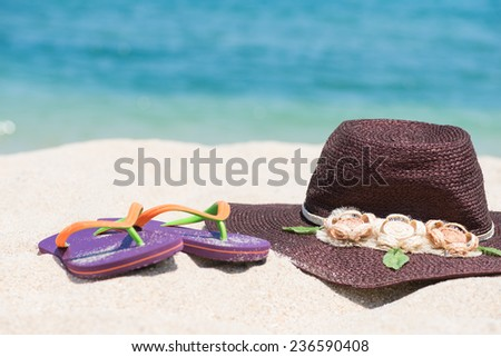 Straw hat and flip flops on sandy beach with blue sea background  - stock photo