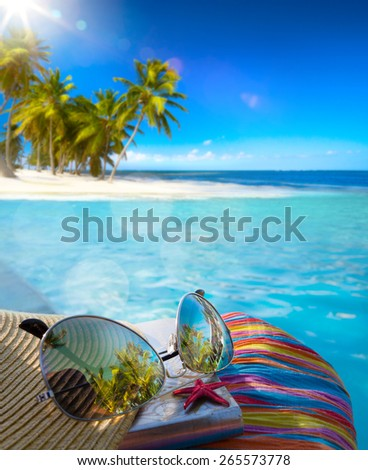 Straw hat, bag and sun glasses  on a tropical beach  - stock photo