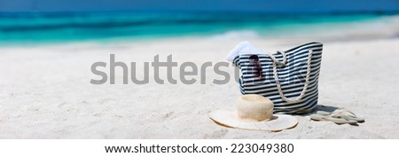 Straw hat, bag, sun glasses and flip flops on a tropical beach. Wide panorama, perfect for banners - stock photo