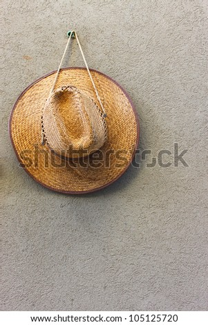 straw hat hang on a textured wall - stock photo