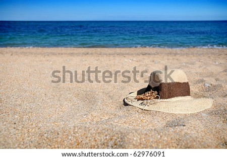 Straw hat lying in the sand on the beach - stock photo