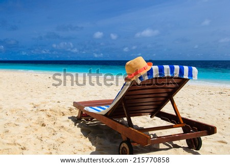 straw hat on a lounge chair at tropical sand beach - stock photo