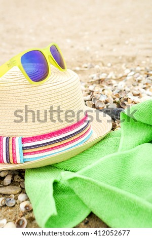 Straw hat, sunglasses and on a sandy beach background