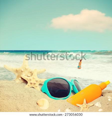 Straw hat, sunglasses, towel and starfish on sand beach. - stock photo