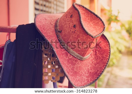 Straw hat with gloves on a bale of hay in barn - stock photo