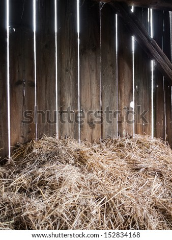 Straw in the old barn with timber wall - stock photo