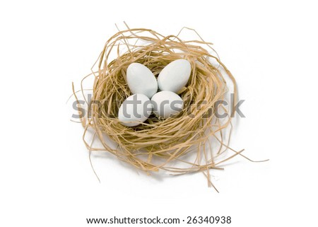 Straw nest with four white coated chocolate eggs, on white background.