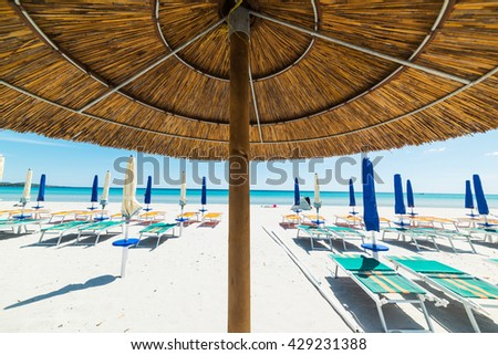 straw parasol with closed umbrellas in the background