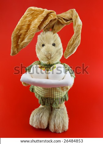 Straw rabbit with eggs in hands on red background.