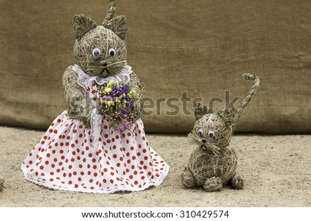 straw sculpture of cat and kitten - stock photo