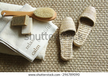 Straw slippers with spa accessories on carpet - stock photo