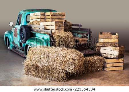 straw, stacks of old wood boxes and green truck for background - stock photo